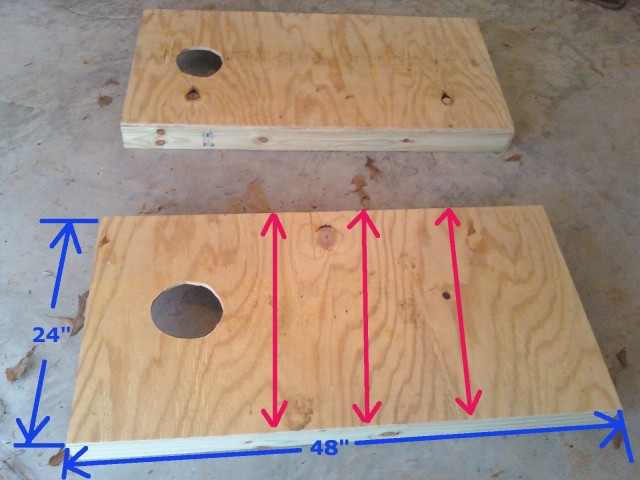 2 unfinised cornhole boards on ground with correct graphics